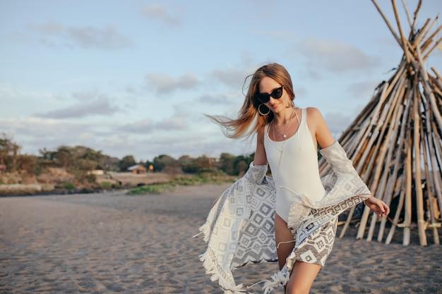 Pleased blonde woman walking around sandy beach in morning.