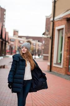 キエフの路上でポーズをとって黒い冬のコートとニット帽を身に着けている満足しているブロンドの女性