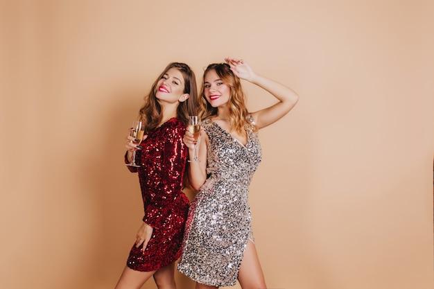 새해 파티에서 친구와 함께 포즈를 취하고 가벼운 벽에 웃고 붉은 입술로 기쁘게 금발의 여자