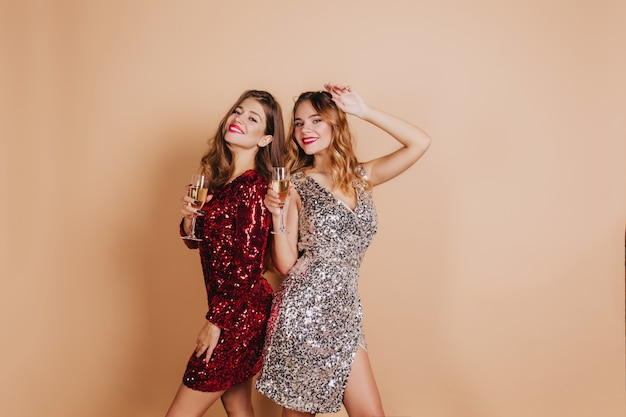 Pleased blonde woman with red lips posing with friend at new year party and laughing on light wall