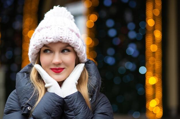 ボケと花輪の背景の上で通りでポーズをとってニット帽をかぶった赤い口紅で喜んで金髪の女性