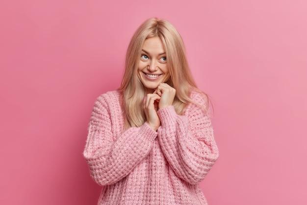 Felice giovane donna bionda tiene le mani unite e ha un'espressione del viso positivo sognante vestito con un maglione lavorato a maglia sciolto