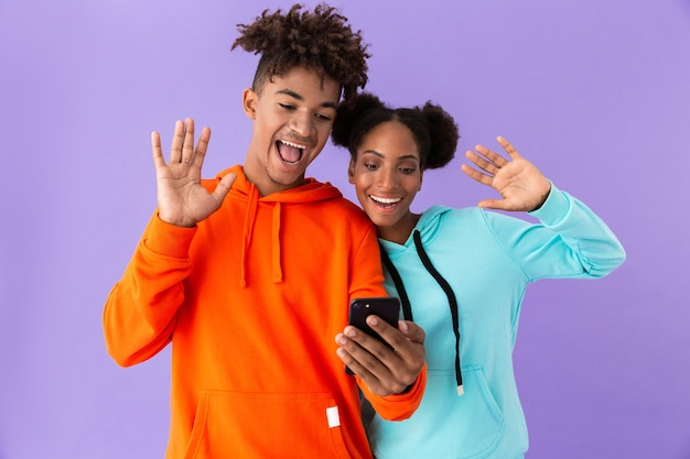 Pleased brother and sister wearing colorful sweatshirts using mobile phone, isolated over violet wall