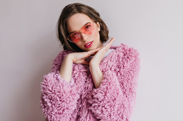 Pleased brown-haired young woman in bright sunglasses chillng during photoshoot. indoor portrait of beautiful caucasian girl in fur coat posing with interest.