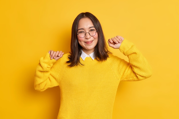 Pleased brunette asian woman feels relieved raises arms and smiles with pleasure wears round spectacles jumper.