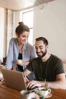 Pleased brunette couple man and woman drinking coffee and working on laptop together while sitting at table at home