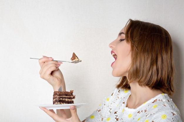 甘いチョコレートケーキを食べる自然な化粧でブルネットの女性を喜ばせます。テキスト用のスペース
