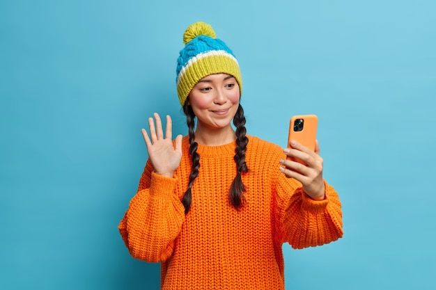 Pleased brunette pretty millennial girl waves palm greets friend online holds modern cellular makes video call wears warm knitted sweater and hat isolated over blue wall