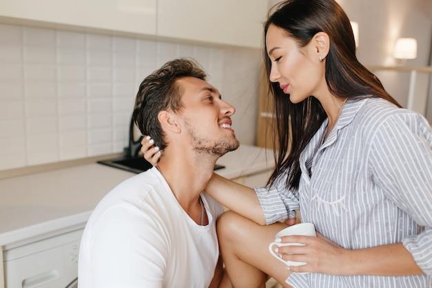 コーヒーを飲み、夫の髪をなでるパジャマで幸せなブルネットの女性