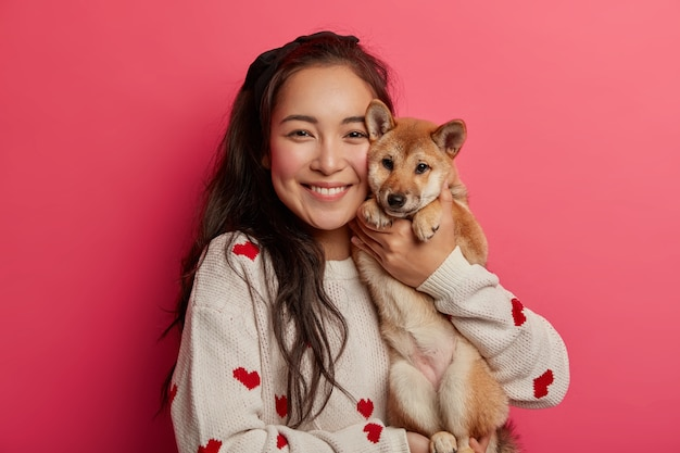 Pleased brunette woman plays with pedigree dog, embraces shiba inu, enjoys spare time, expresses loyalty from four legged friend, carries animal to vet clinic, has toothy smile.