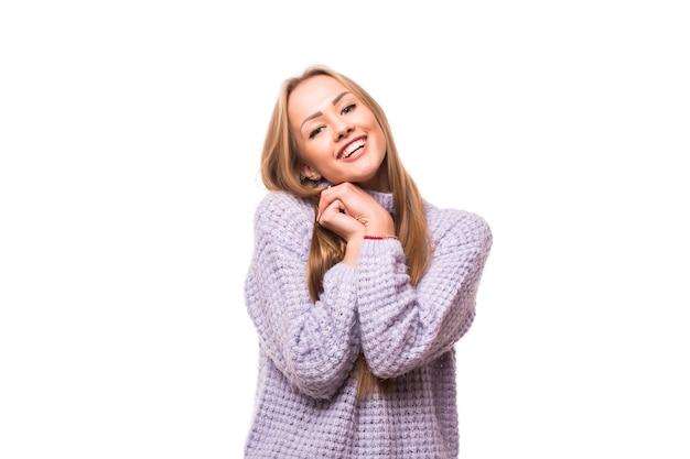 Довольная брюнетка женщина возлежит на руках над белой стеной