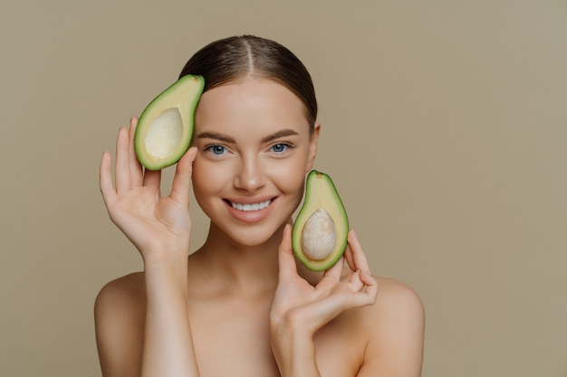 Pleased brunette woman smiles gently holds halves of avocado