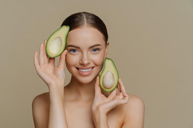 Довольная брюнетка женщина улыбается нежно держит половинки авокадо