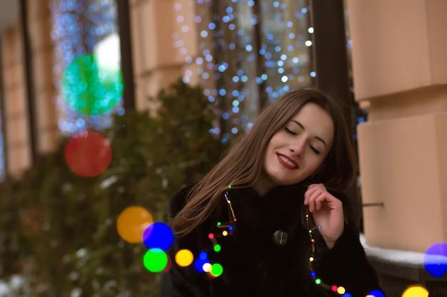 彼女の手に花輪でポーズをとって毛皮のコートを着ている幸せなブルネットの女性