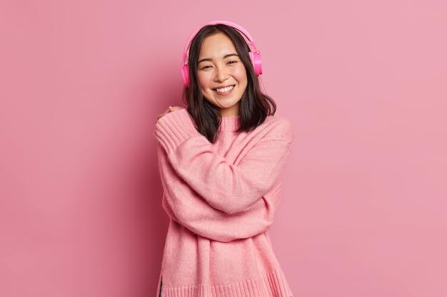 동양의 모습을 가진 만족스러운 갈색 머리 여자가 느슨한 스웨터를 입고 미소를 지으며 전자 헤드폰을 통해 좋아하는 음악을 듣는 것을 즐깁니다.