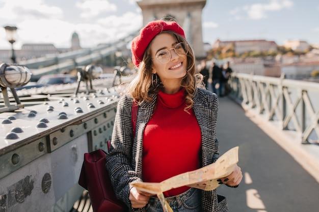 Довольная брюнетка женщина с красным рюкзаком позирует на мосту на городском фоне