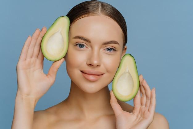 Pleased brunette young european female model holds halves of avocado near face