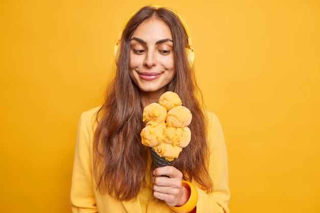 Pleased brunette young european woman enjoys eating delicious ice cream listens music via headphones has day off isolated over vivid yellow wall. spare time leisure and summer concept.