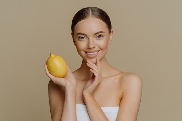 Pleased brunette young woman wrapped in bath towel holds lemon for making facial mask