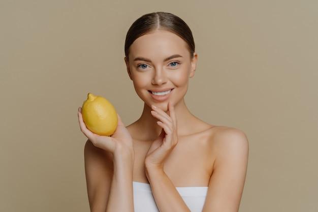 バスタオルに包まれた幸せなブルネットの若い女性は、顔のマスクを作るためにレモンを保持します