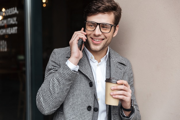 Pleased businessman in eyeglasses and coat talking by smartphone