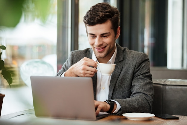 Pleased businessman sitting by the table in cafe while holding cup of coffee and using laptop computer