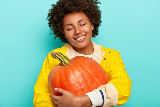 Pleased calm afro woman harvesting pumpkin, tilts head, closes eyes and smiles broadly, wears yellow raincoat, enjoys autumn time and holidays, isolated