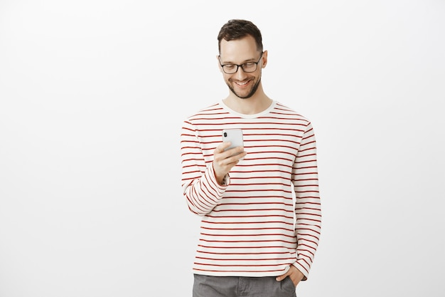 Pleased carefree handsome man with bristle in glasses, holding hand in pocket while brosing in net via smartphone