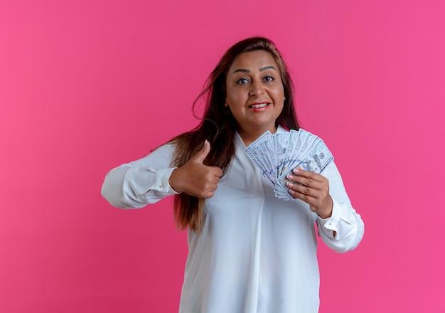 親指を立てて現金を持っている幸せなカジュアルな白人の中年女性