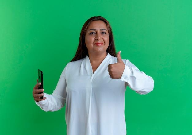 親指を立てて電話を持っている幸せなカジュアルな白人の中年女性