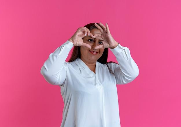 Donna di mezza età caucasica casuale soddisfatta che mostra il gesto del cuore