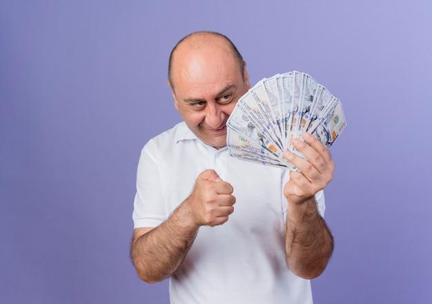 Felice casual imprenditore maturo azienda e guardando i soldi e il pugno di serraggio isolato su sfondo viola con copia spazio