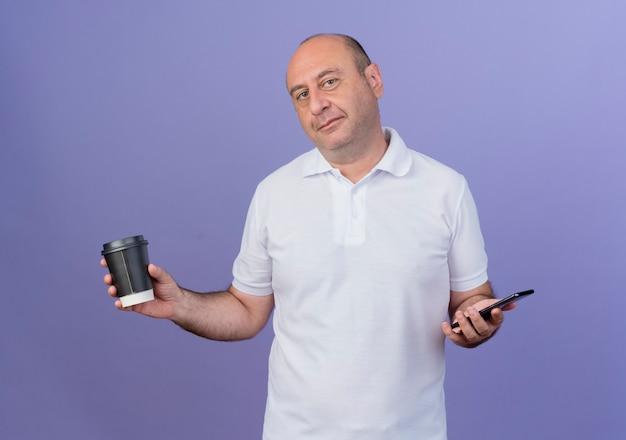 휴대 전화와 보라색 배경에 절연 플라스틱 커피 컵을 들고 기쁘게 캐주얼 성숙한 사업가