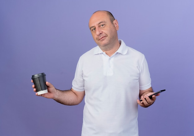Pleased casual mature businessman holding mobile phone and plastic coffee cup isolated on purple background