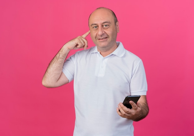Pleased casual mature businessman holding mobile phone and putting finger on ear isolated on pink background with copy space