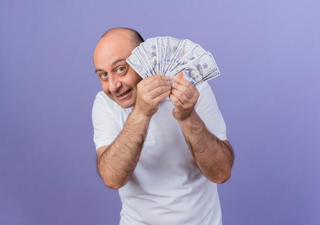 Довольный случайный зрелый бизнесмен держит деньги и смотрит в камеру из-за денег, изолированных на фиолетовом фоне с копией пространства
