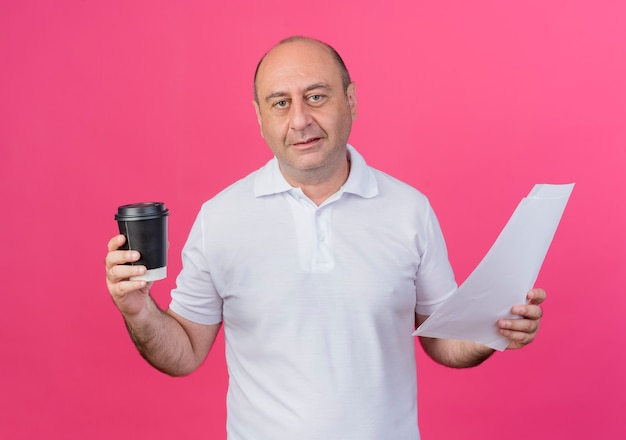 플라스틱 커피 컵과 분홍색 배경에 고립 된 문서를 들고 기쁘게 캐주얼 성숙한 사업가