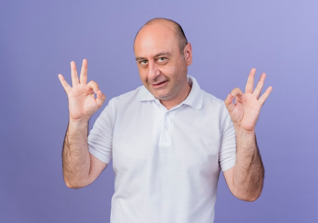 Pleased casual mature businessman looking at camera and doing ok signs isolated on purple background