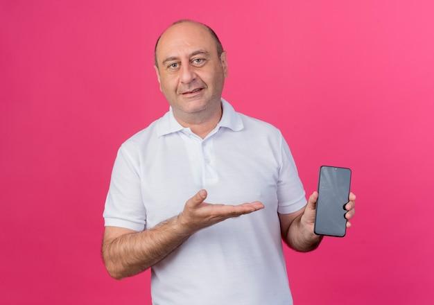 휴대 전화를 표시하고 분홍색 배경에 고립 된 손으로 가리키는 기쁘게 캐주얼 성숙한 사업가