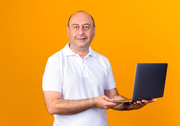 黄色の背景に分離されたラップトップを保持している幸せなカジュアルな成熟した男 無料写真