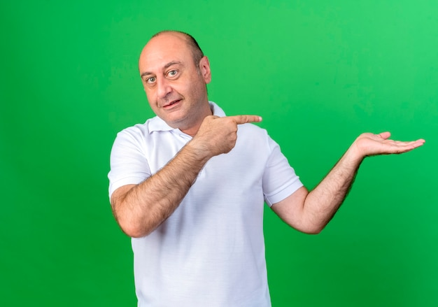 Pleased casual mature man pretending holding and points at something