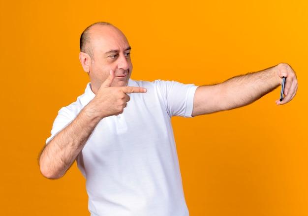 Довольный случайный зрелый мужчина делает селфи и указывает на телефон, изолированный на желтой стене