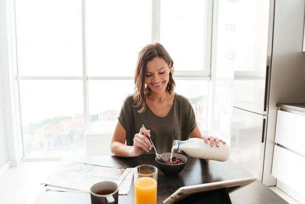 キッチンのテーブルで食べてタブレットコンピューターを見て満足しているカジュアルな女性