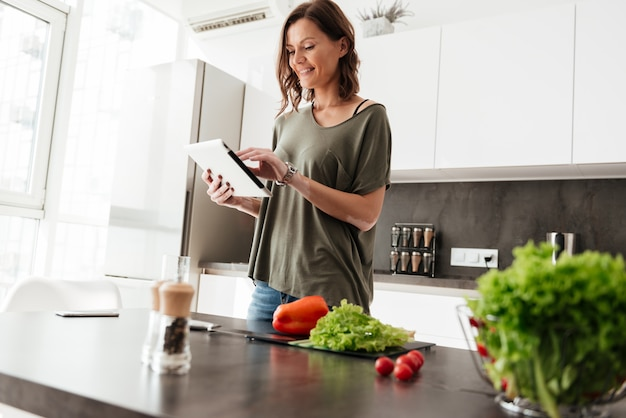 Pleased casual woman using tablet computer while standing near the table on kitchen