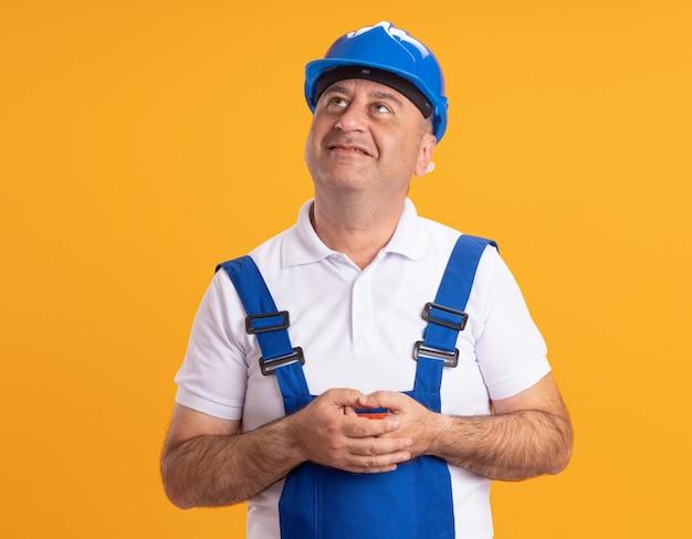 Felice uomo adulto caucasico costruttore in uniforme tiene le mani insieme e guarda in alto sull'arancia