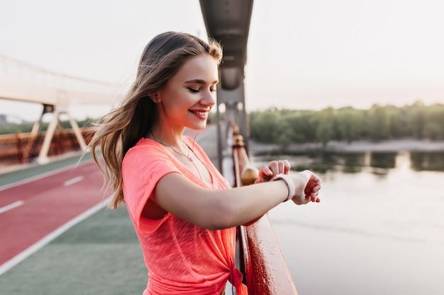 Довольная кавказская девушка в повседневной футболке с помощью фитнес-браслета. открытый выстрел потрясающей дамы, улыбающейся после тренировки.