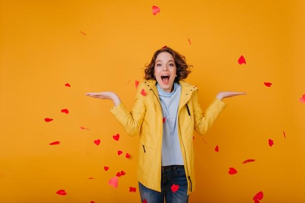 Довольная кавказская девушка в стильной желтой куртке, выражающая счастье в день святого валентина. веселая женская модель с волнистыми волосами, выбрасывающими сердца.