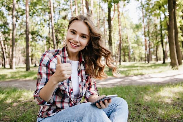 Довольная кавказская дама сидит на земле с телефоном в руке. открытый портрет веселой белокурой девушки в повседневной одежде, позирующей на лужайке.