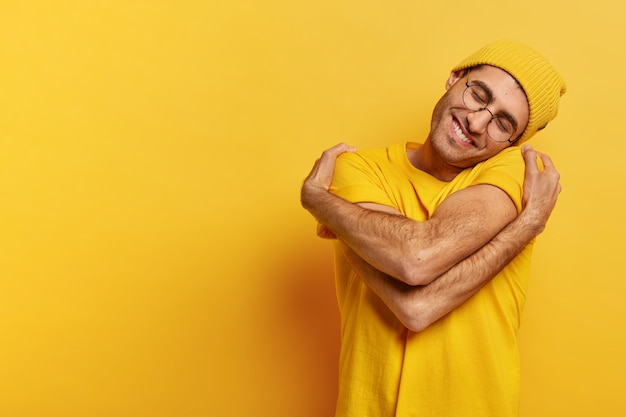 Pleased caucasian man hugs himself, has high self esteem, tilts head, has toothy smile, wears casual yellow hat and t shirt
