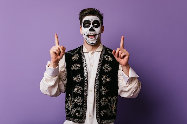 Pleased caucasian man in mexican attire preparing for party. enthusiastic male model with halloween makeup funny posing on purple wall.